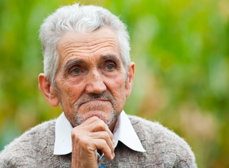 candid: Portrait of a wrinkled and expressive old farmer outdoor