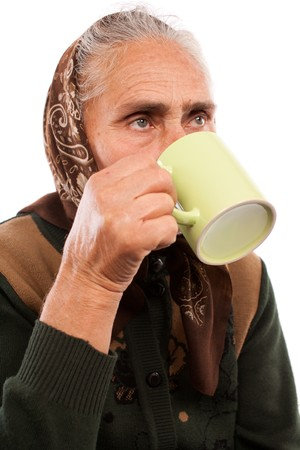Closeup portrait of an old woman drinking from a cup photo