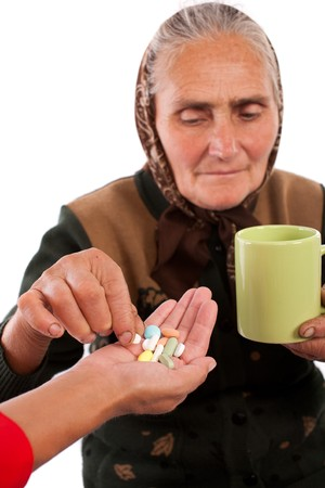Portrait of an old woman taking pills, isolated on white photo