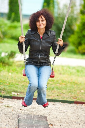 Young caucasian woman swinging in a playground photo
