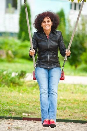 Young caucasian woman swinging in a playground Stock Photo - 7891092