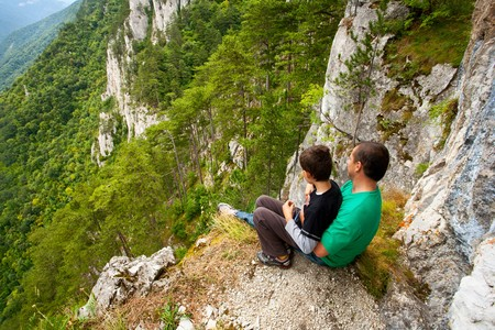 Father and son in mountains, sitting on the edge of a cliff photo