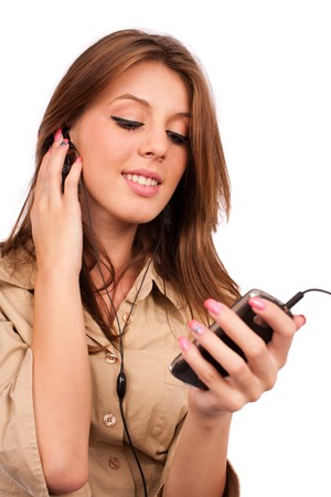 Portrait of a young lady with earphones listening music to her modern cellphone or handset Stock Photo - 7914304