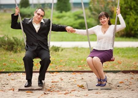 columpios: J�venes de hombre y mujer en columpios al aire libre en un parque