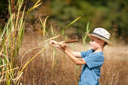 Cute boy with straw hat playing with bulrush outdoor photo