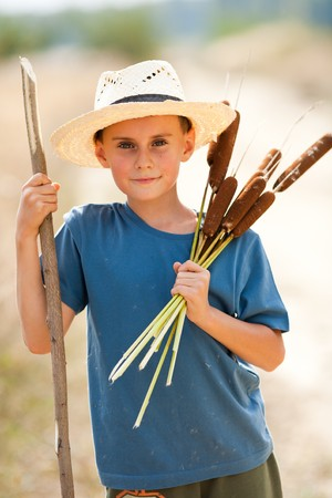 Cute boy with straw hat playing with bulrush outdoor Stock Photo - 7999310