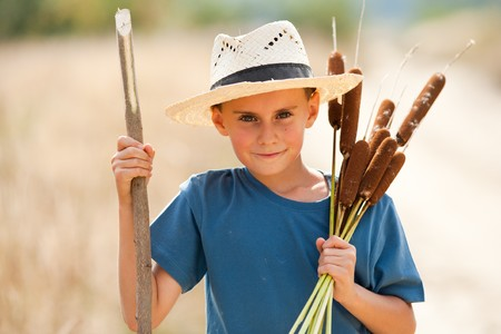 Cute boy with straw hat playing with bulrush outdoor Stock Photo - 7999307