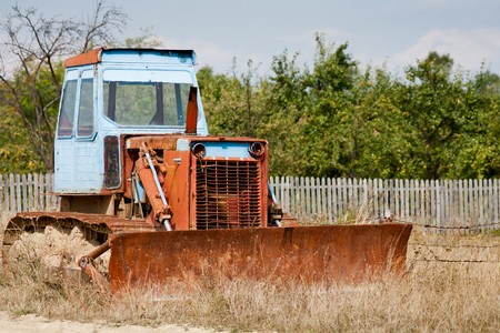 Abandoned and rusty bulldozer near a forest photo
