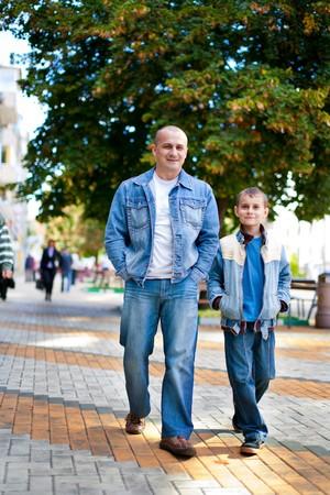 padres hablando con hijos: Padre e hijo, pasear al aire libre en un parque  Foto de archivo