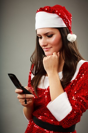 Beautiful Christmas girl speaking on cellphone with Santa, studio shot photo
