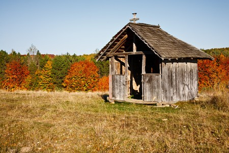 Wooden vintage shack near the forest in autumn