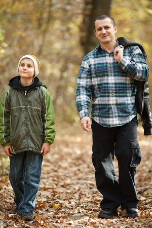 fallen tree: Father and son talking a walk outdoor in a forest, in an autumn day