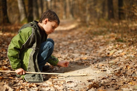dirt on ground: Cute kid writing on the ground with a stick in the forest Stock Photo