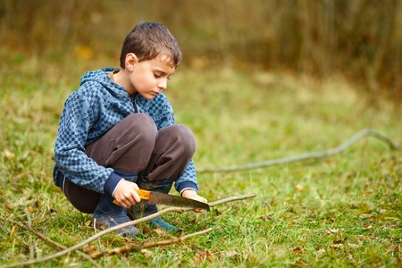 preoccupied: Cute kid cutting birch with a handsaw to make bow and arrows to play with