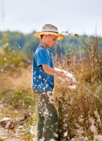 Cute kid with farmer hat playing with bulrush outdoor Stock Photo - 8336160