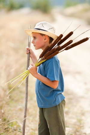 Cute kid with farmer hat playing with bulrush outdoor Stock Photo - 8336157