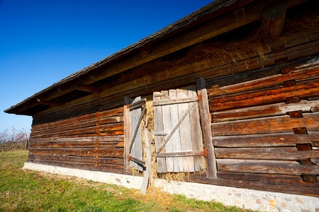 Old traditional Romanian barn or shack under blue sky - this is part of a series of images with countryside buildings in Romania photo
