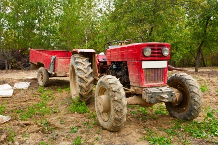 Old tractor and trailer in an orchard photo