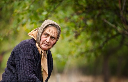 Portrait of an expressive old woman outdoor in an orchard