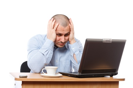Tired and stressed young businessman working at his computer Stock Photo - 8395926
