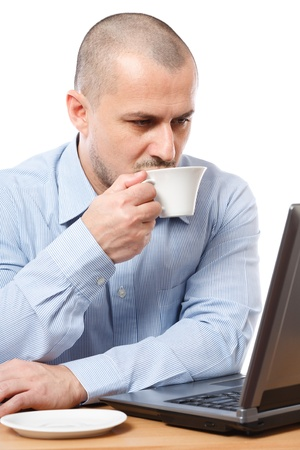 Young businessman drinking coffee while reading on the computers screen