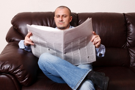 Young man reading newspaper on a leather sofa Stock Photo - 8395943