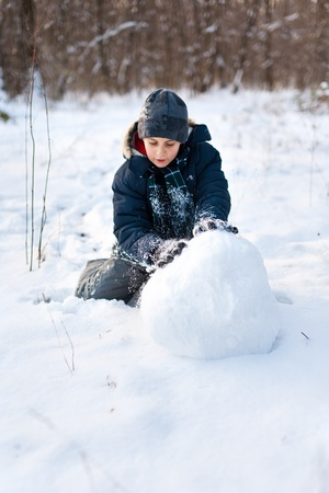 Happy kid playing in the snow near a forest photo