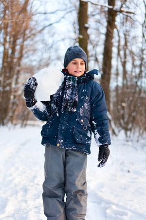 Happy cute boy playing in the snow near a forest photo