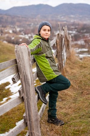 Little boy sitting on a wooden fence in the countryside Stock Photo - 8553473