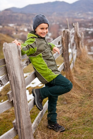 Little boy sitting on a wooden fence in the countryside Stock Photo - 8553476
