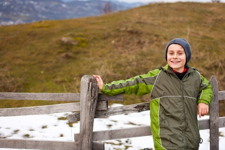 Little boy sitting on a wooden fence in the countryside Stock Photo - 8553436
