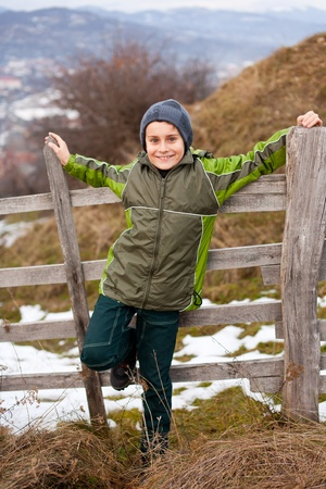 Little boy sitting on a wooden fence in the countryside Stock Photo - 8553478