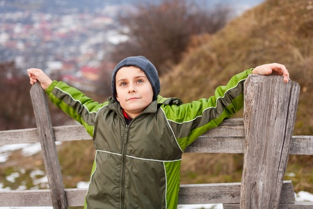 Little boy sitting on a wooden fence in the countryside Stock Photo - 8553464