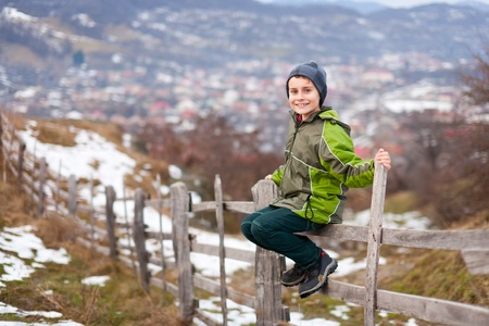 Little boy sitting on a wooden fence in the countryside Stock Photo - 8553378