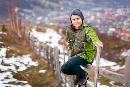 Little boy sitting on a wooden fence in the countryside photo