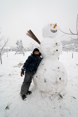 Kid nearby a big snowman in a winter landscape photo
