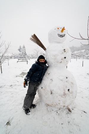 Kid nearby a big snowman in a winter landscape photo