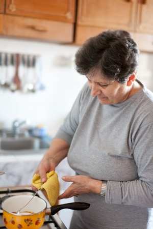 Senior woman cooking on a stove in bright daylight photo
