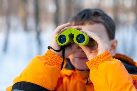 Little boy with binoculars in the forest in a winter day photo