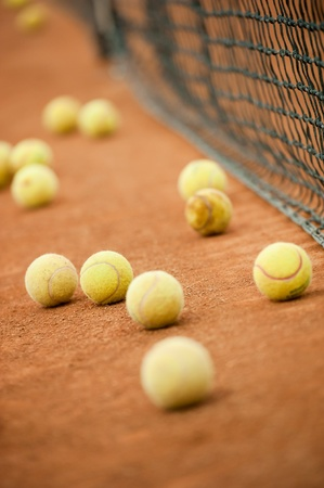 Many yellow tennis balls on a slag field near the net photo