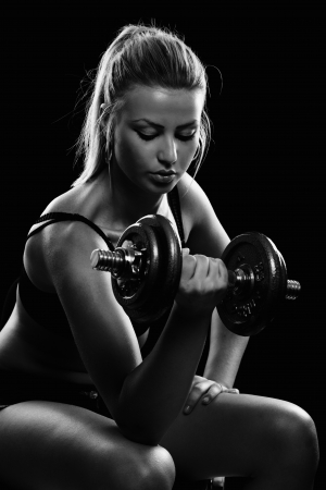 Athletic young lady doing workout with weights photo