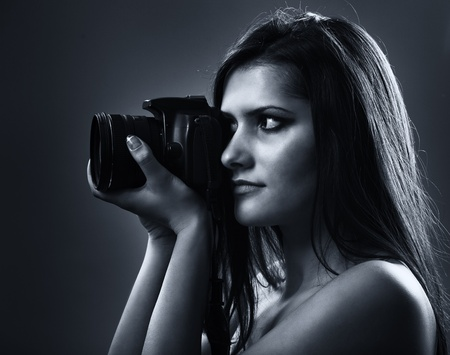 Portrait of a beautiful young woman using dslr camera photo