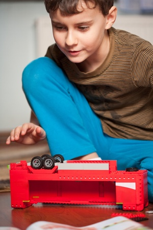 inventive: Kid playing with toys indoor, in his room Stock Photo