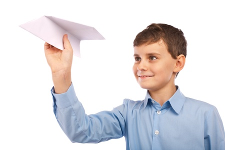 Schoolboy throwing a paper plane, isolated on white background photo
