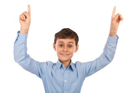Happy schoolboy pointing to the copyspace above, isolated on white background photo