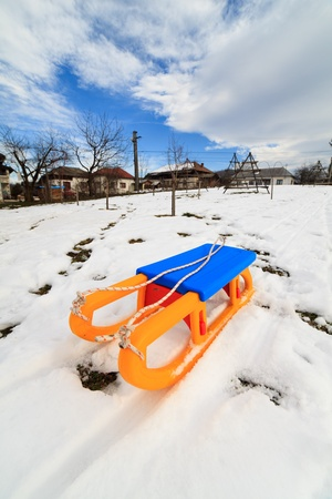 Countryside view with a plastic yellow and blue sledge photo