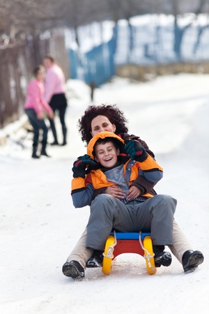 sledging people: Mother and son on a sledge at speed, having fun Stock Photo