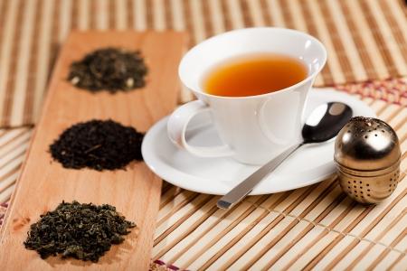 teepflanze: Eine Tasse Tee in der N�he von drei Haufen von verschiedenen Arten von Tee