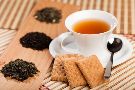 A cup of tea near three piles of various kinds of tea photo