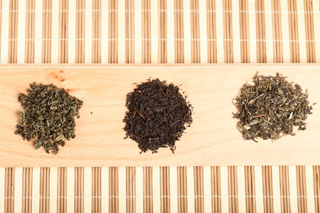 Closeup of three piles with dried leaves tea, of type: jiaogulan, black and green photo